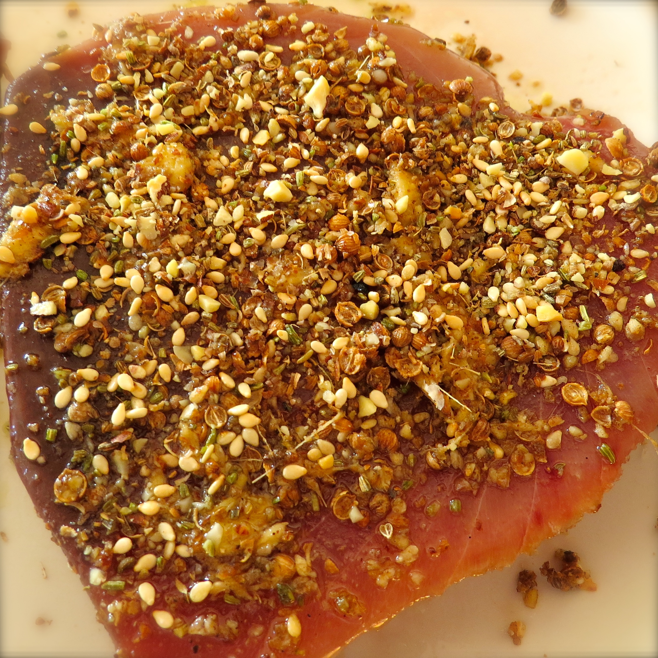 Here's the tuna just after I poured the spice mixture on both sides. After taking this picture, I lightly pressed the spices into the tuna. The olive oil provids the glue.