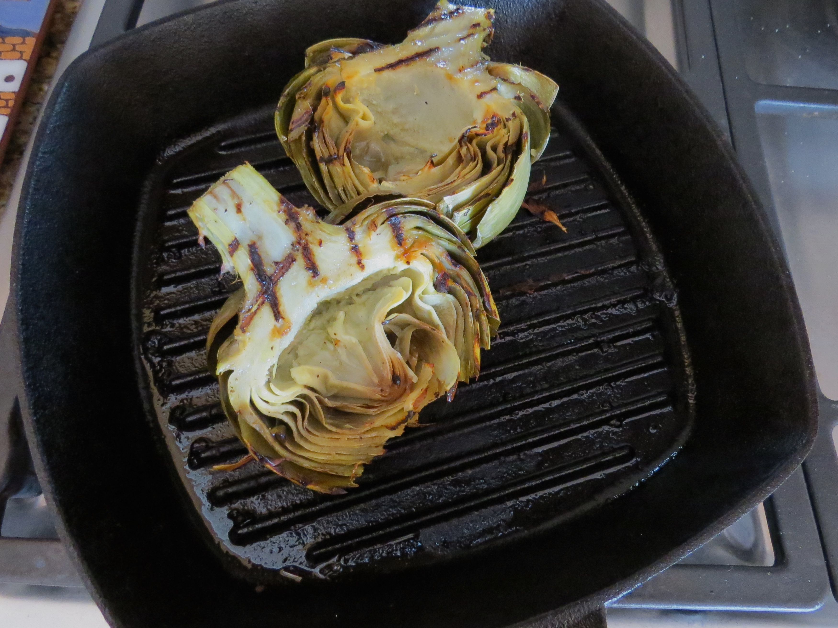 I mixed together 2 sliced garlic cloves, 1 Tbs, lemon juice, 1/2 tsp of salt and pepper and 2 TBS olive oil. After brushing the entire artichoke halves with the mix, I grilled them for 6 minutes, 3 minutes for each side. No condiments needed for serving...so good.