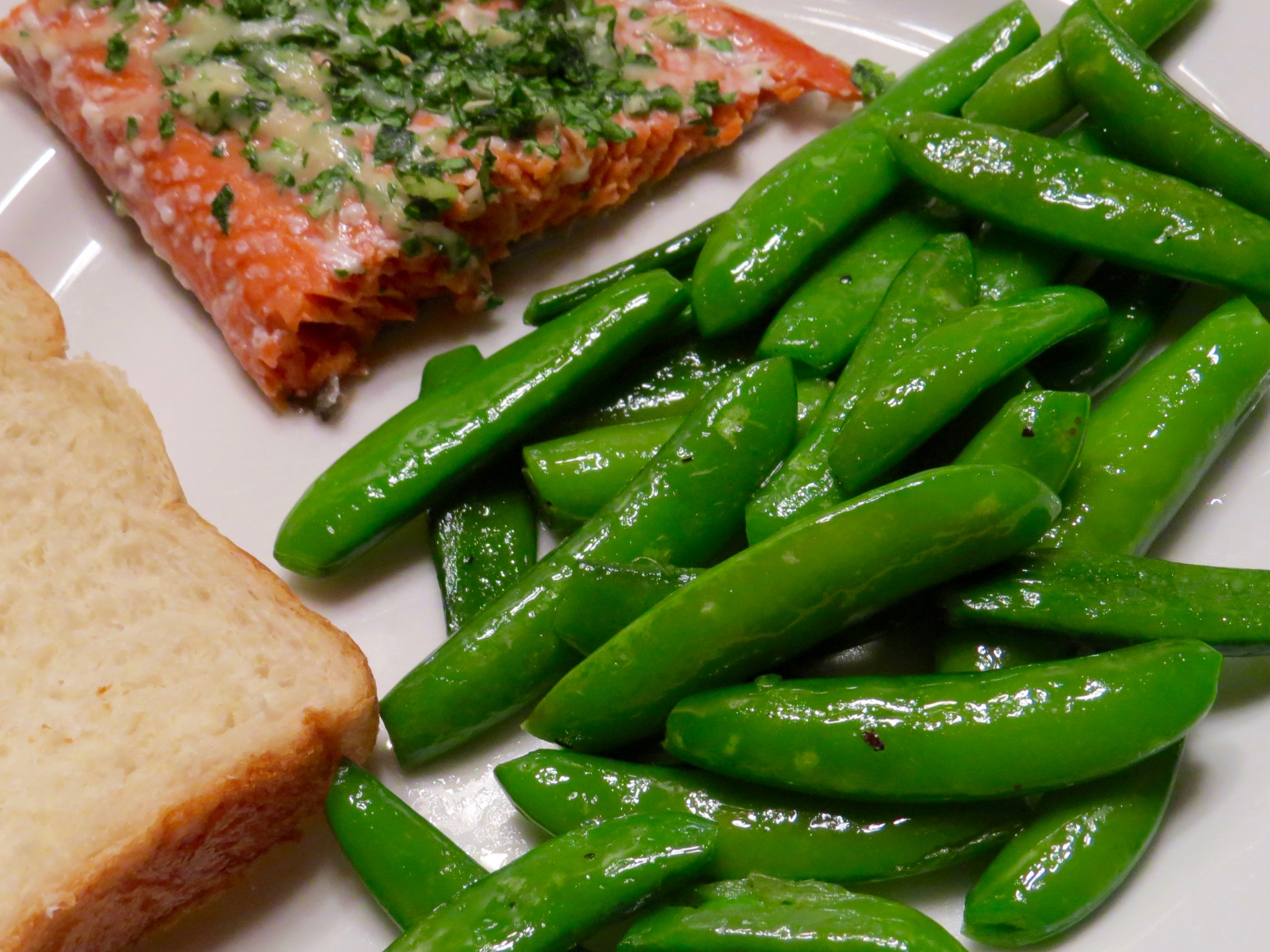 BAKED SALMON WITH PARMESAN HERB CRUST, SAUTEED SUGAR SNAP PEAS AND HOMEMADE BREAD.