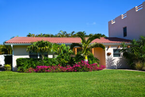 A beautiful Florida home features a Spanish tile roofing system and has a green lawn with palm trees out front.