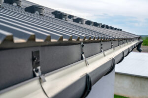 A close-up image of a the edge of a standing-seam metal roofing systems with half-round gutters.