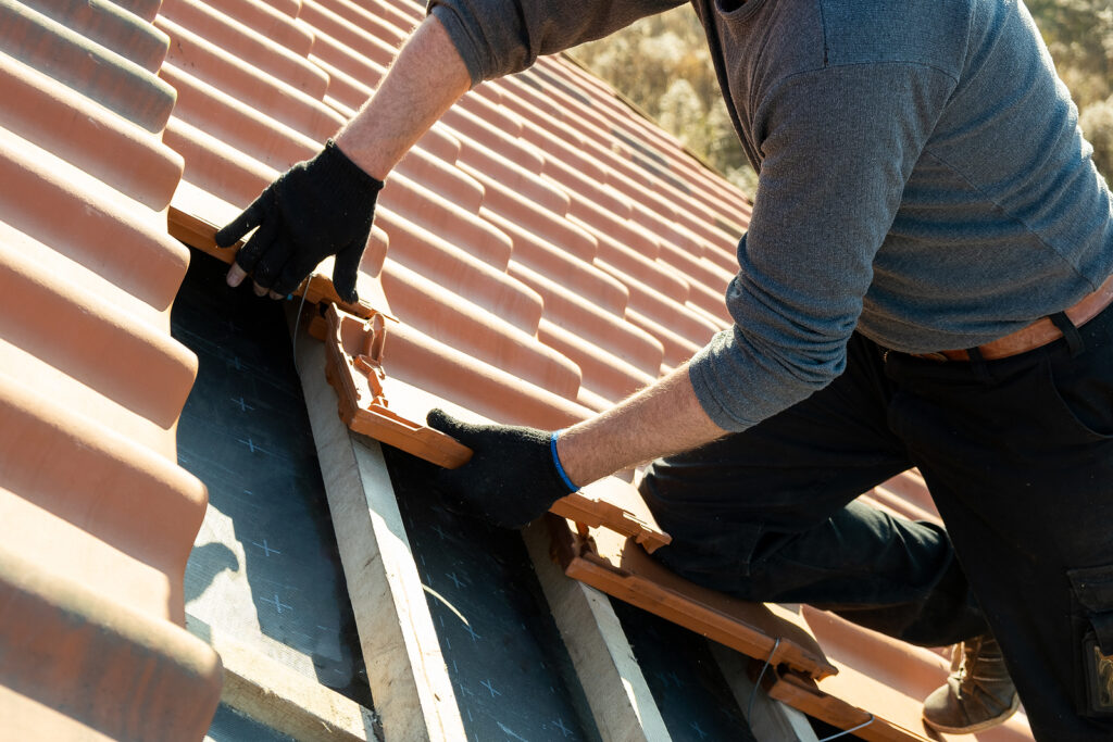 A closeup of a worker installing tile roofing to repair damage.