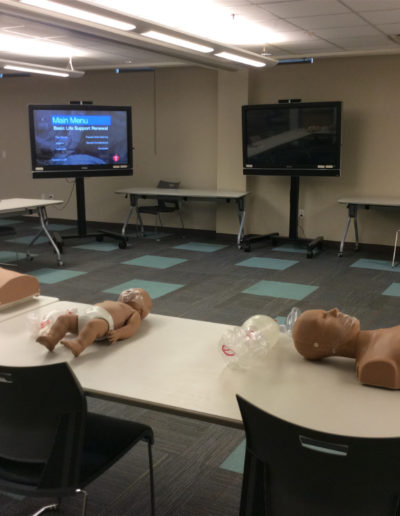 Image of a BLS classroom set-up with manikins, tables, TV monitors and other training gear.