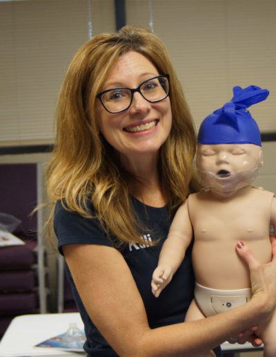 Photo of Kelli holding training manikin with a disposable glove on it's head.