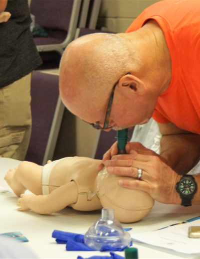Image of student administering infant CPR - breaths into the infant manikin.