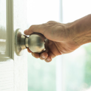 Photo of a hand turning a door knob.