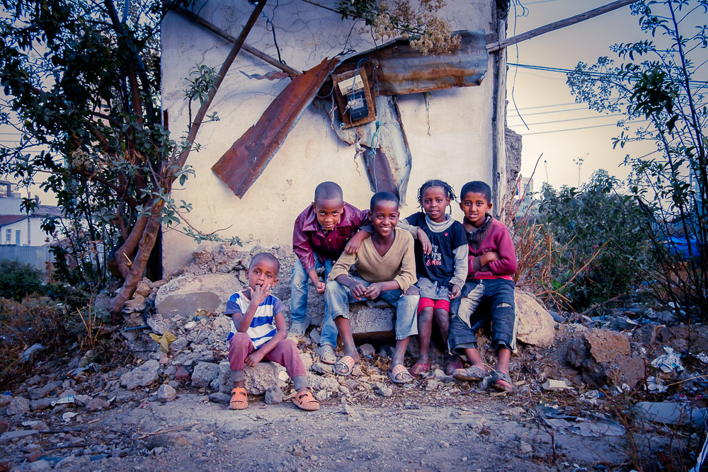 Kids sitting in front of the ruins of a house in Sengatera, Addis Ababa