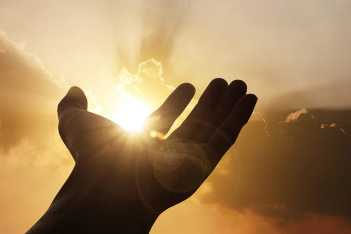 Outstretched hand in sunlight