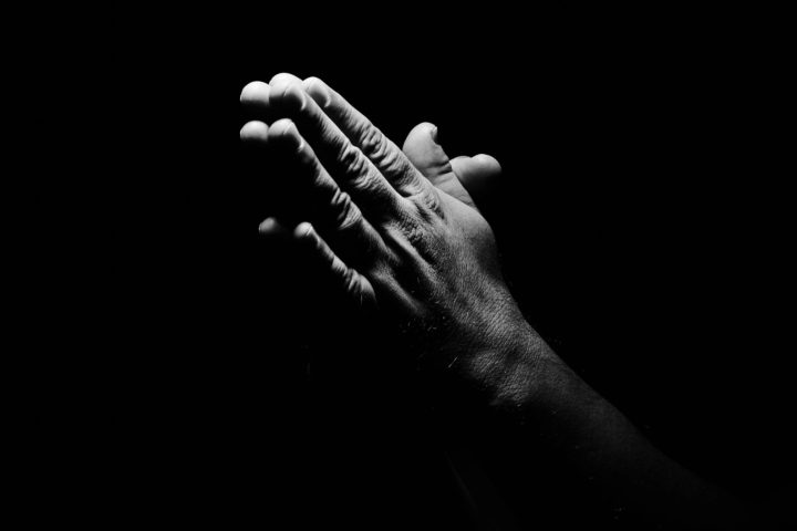 picture of praying hands on black background