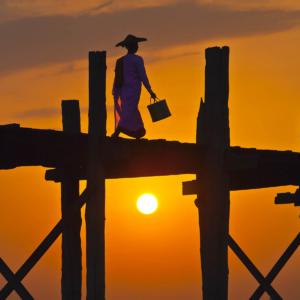 The BURMESE use the teak U BEINS BRIDGE to commute across the Taungthaman Lake at sunrise - AMARAPURA, MYANMAR