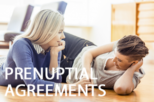 Two women laying on the floor with prenuptial agreements written in white text in front of them.