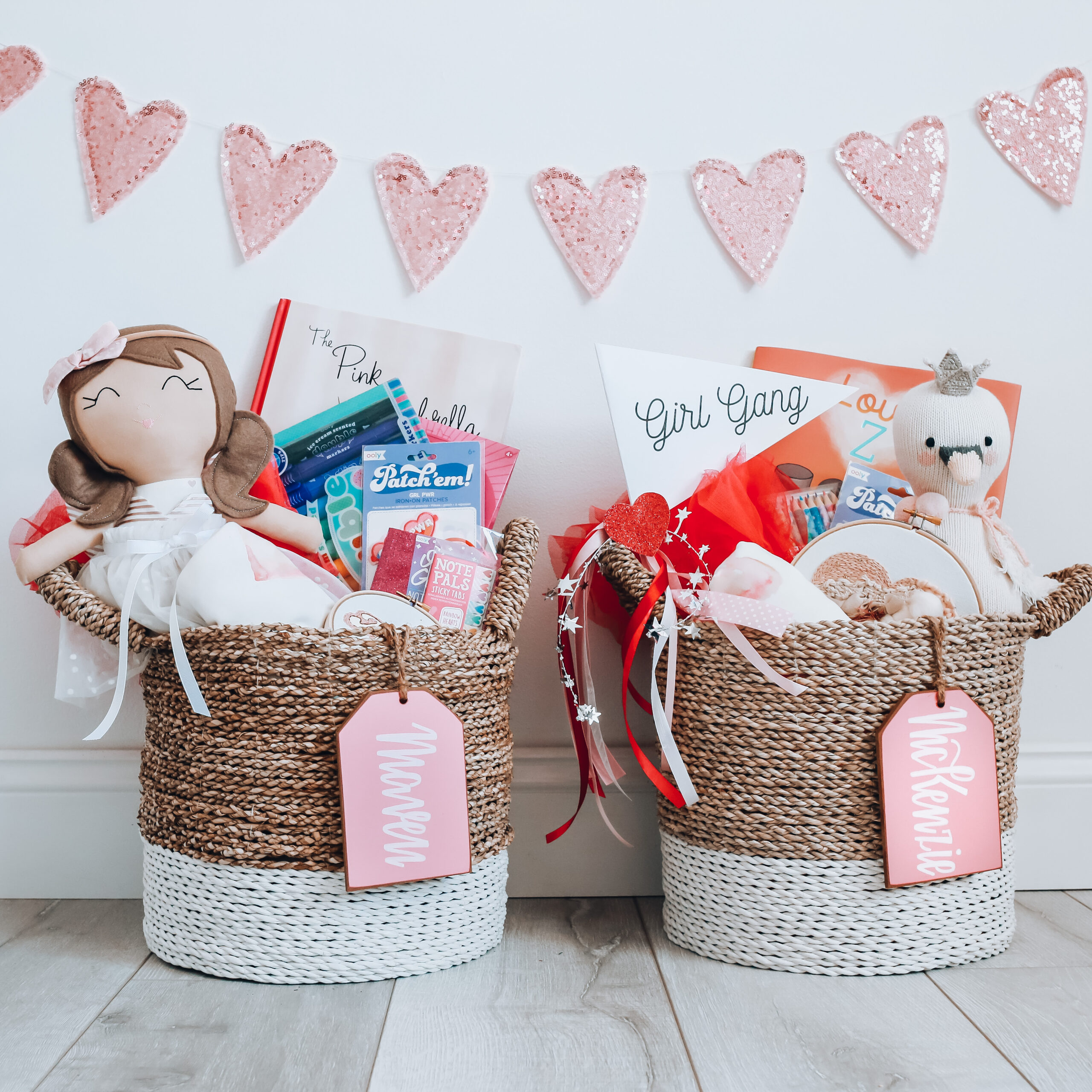 Two seagrass baskets with doll, stuffed animal and Valentine candy with two pink name tags.
