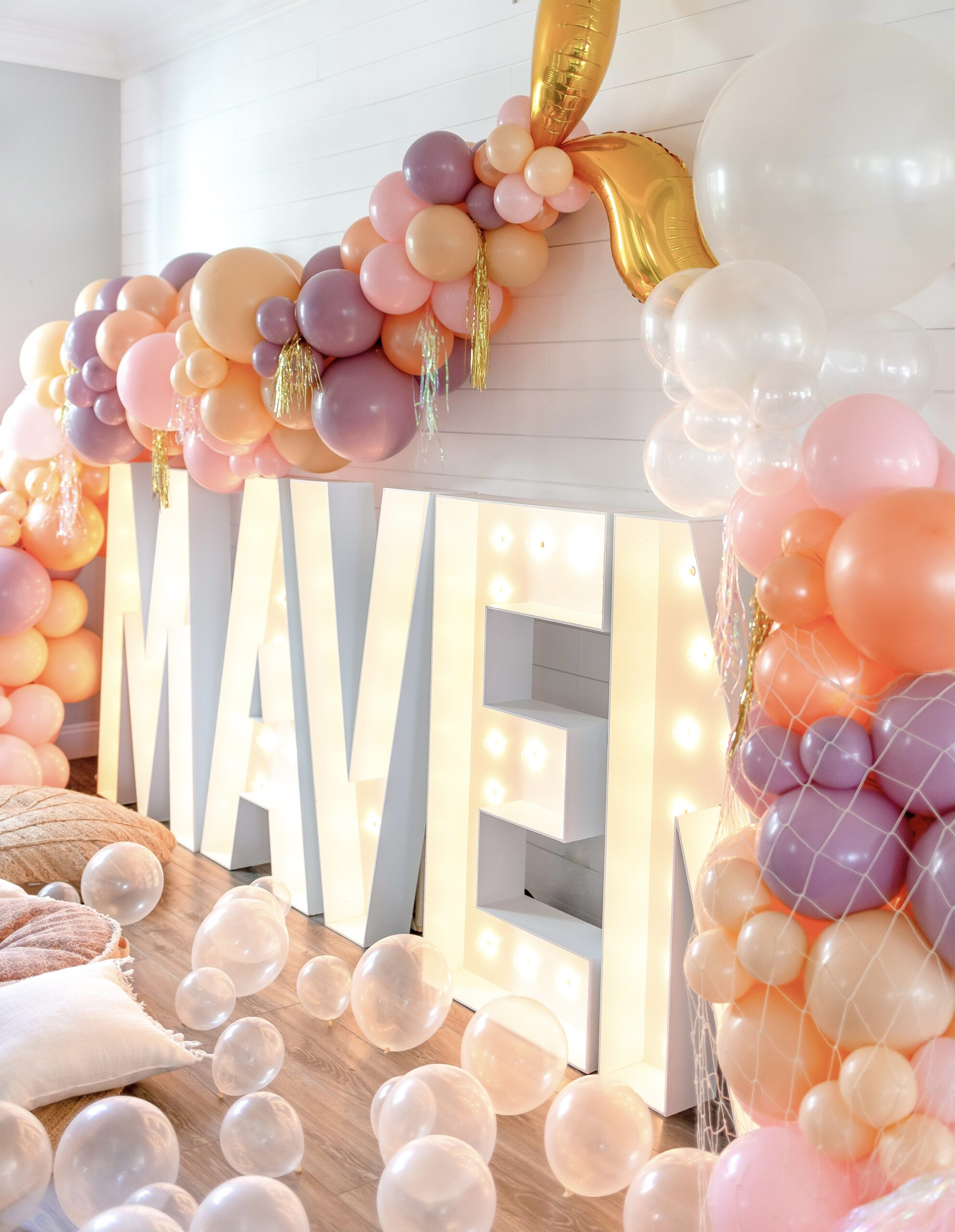Maven in light up letters with purple, pink, peach and cream balloons in the shape of a mermaid tail