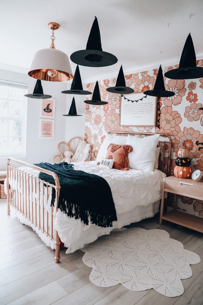 Black witch hats hanging in girls bedroom with floral wallpaper