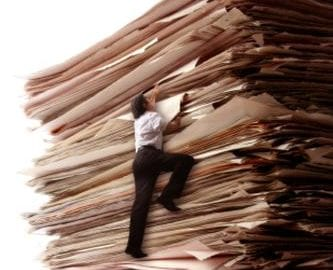 A Business Men Climbing a Pile of Papers
