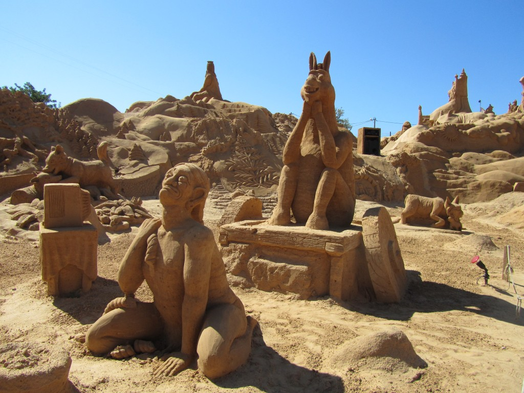 Sand sculpture of a man pulling a donkey on a cart