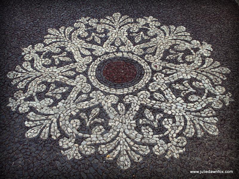 Calçada Portuguesa in black, white and red volcanic basalt. Fancy patterned pavement, Funchal Madeira
