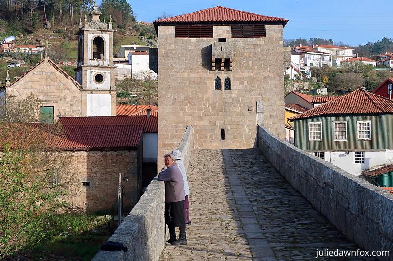 Elderly women looking over an old bridge, Ucanha, Douro Valley Portugal