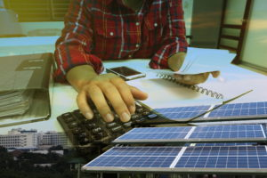 person using calculator to review solar panel installer quotes