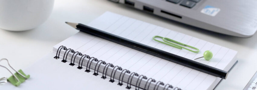 Blank notebook with pencil, paperclip, and computer