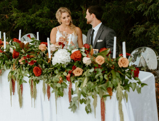Bride and groom in garden at head table