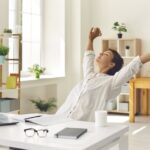 Woman stretches at her desk
