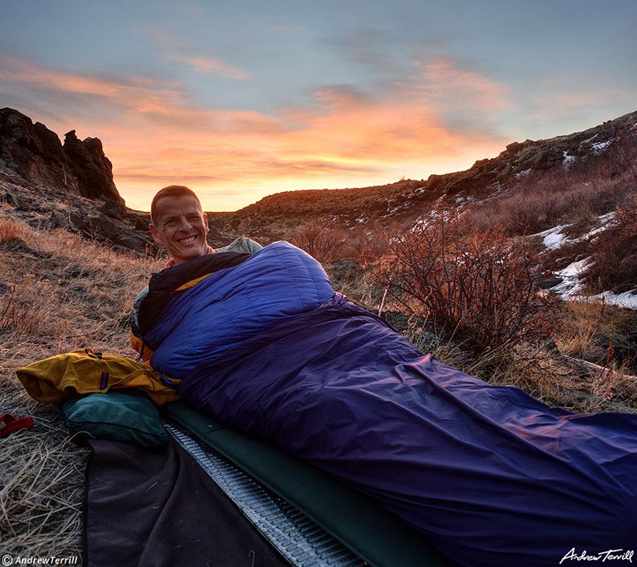 andrew terrill hiker in sleeping bag and bivvy bag at sunrise cowboy camping