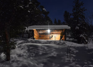 appalachian lean to cabin shelter in moonlit winter forest in snow in golden gate canyon state park colorado
