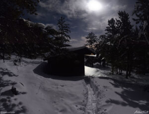 appalachian lean to shelter beneath moon in forest and snow in golden gate canyon state park colorado