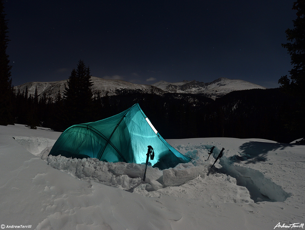 glowing tent in snow during a winter night in rocky mountains colorado