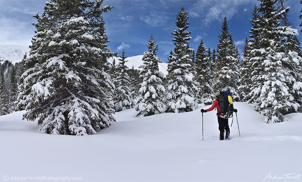 hiker hiking on snowshoes in deep snow in colorado winter mountains