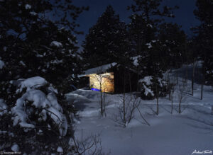 lights in appalachian lean to shelter in moonlit winter forest in golden gate canyon state park colorado