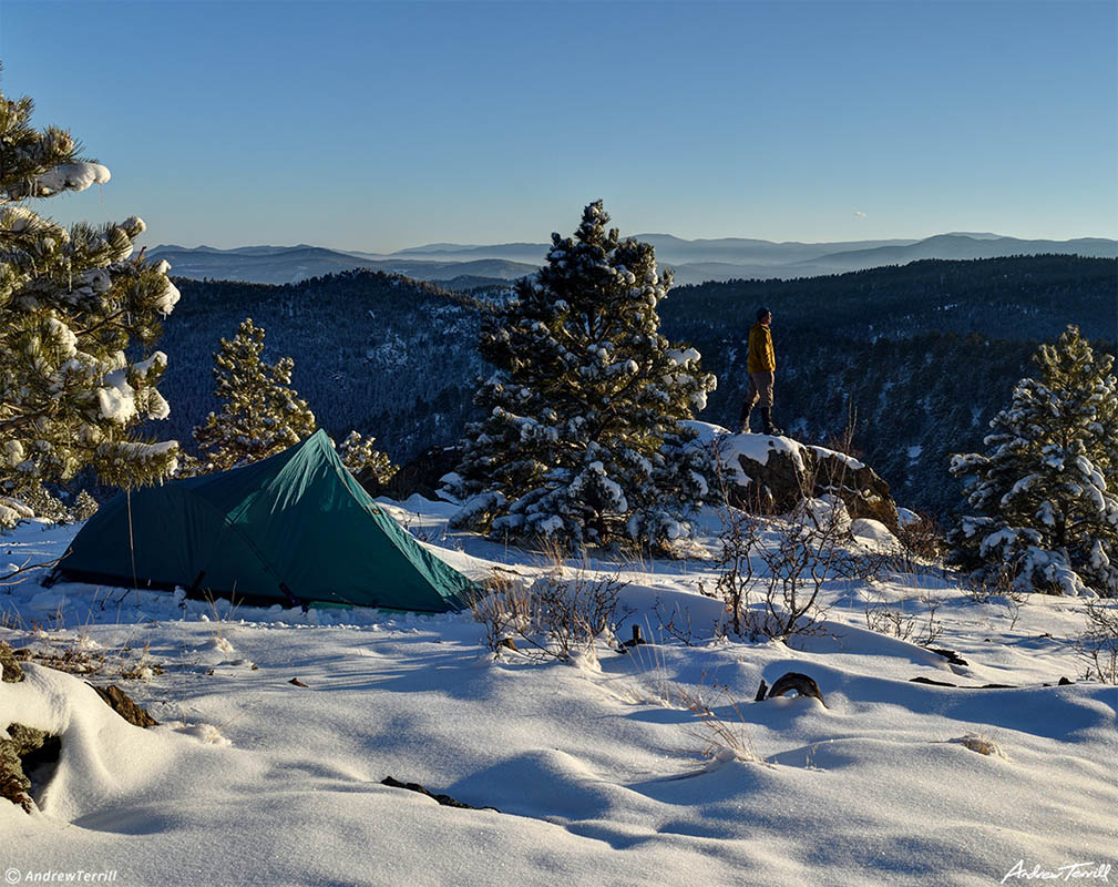 winter camp in snow in front range foothills colorado with tent and lone figure camping