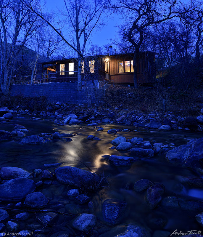 a cabin by a creek in colorado at night