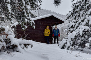 andrew terrill and igloo ed beside wooden cabin colorado