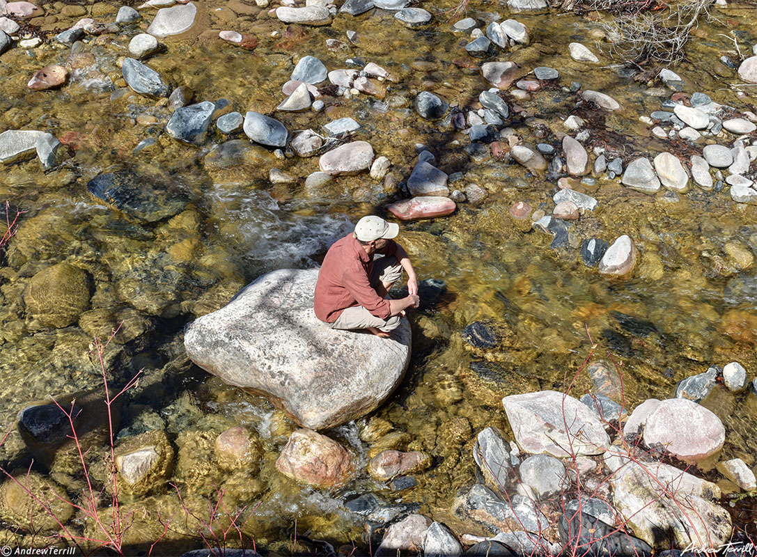 andrew terrill sitting on rock in creek