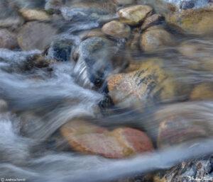 blurred water rushing across river stones in creek