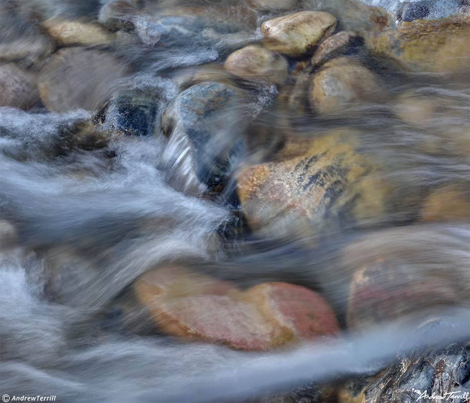 blurred water rushing across river stones in creek