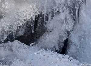 close up of rocks and ice with icicles in mountain creek winter