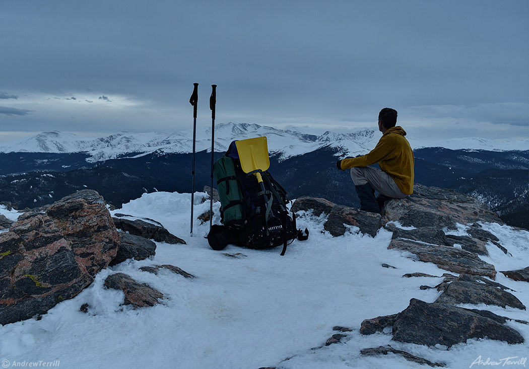 hiker sitting on snowy summit near mount evans april 2021