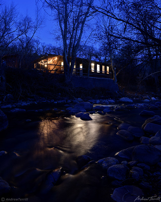 mountain cabin by creek with lights reflecting in water
