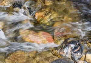 mountain creek gushing downhill blurred water