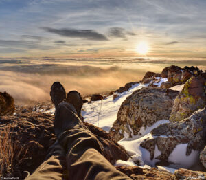 stretching out feet towards sunrise above the clouds