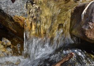 water gushing between rocks small waterfall