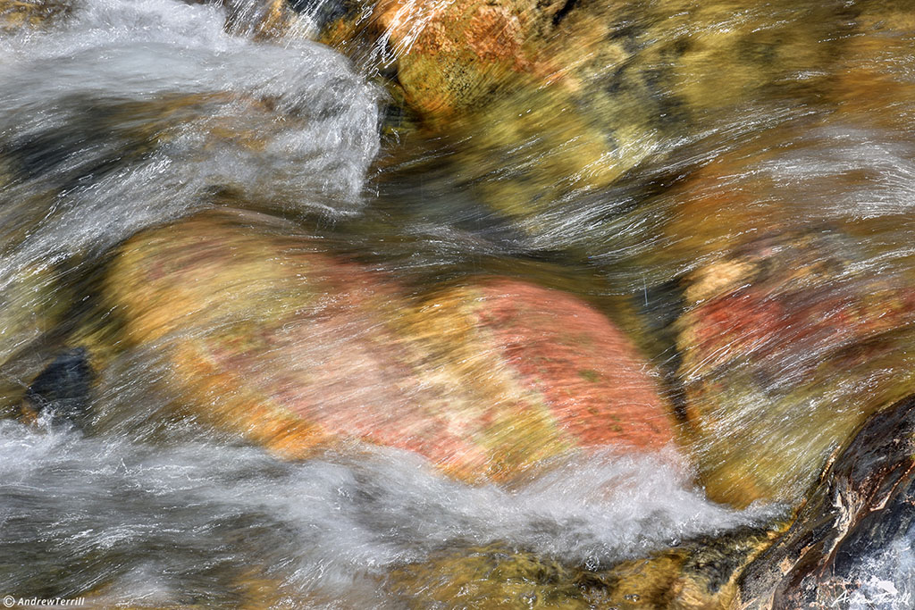 water rushing over colorful river rocks