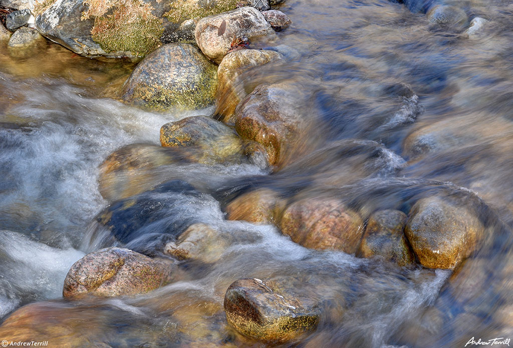 water rushing over river rocks and pebbles