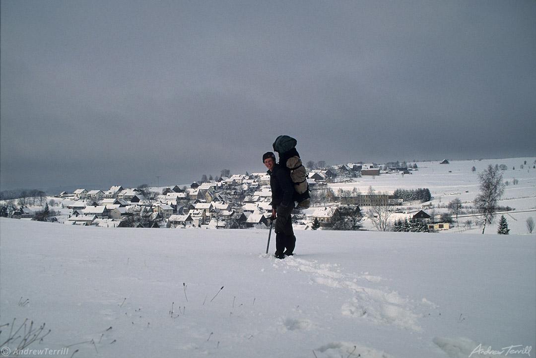 hiker andrew terrill approaching village in winter landscape austria