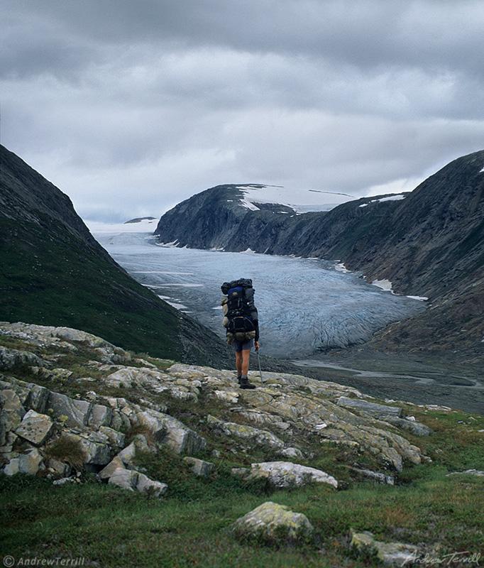 hiker on rocks near glacier in svartisen wilderness norway