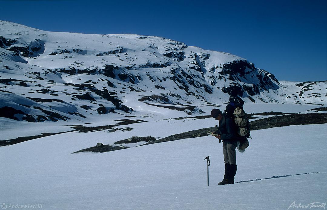 hiker using map in snow winter wilderness norway hardangervidda