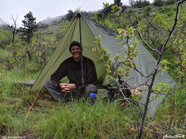 andrew terrill backpacker camping under tarp in the rain
